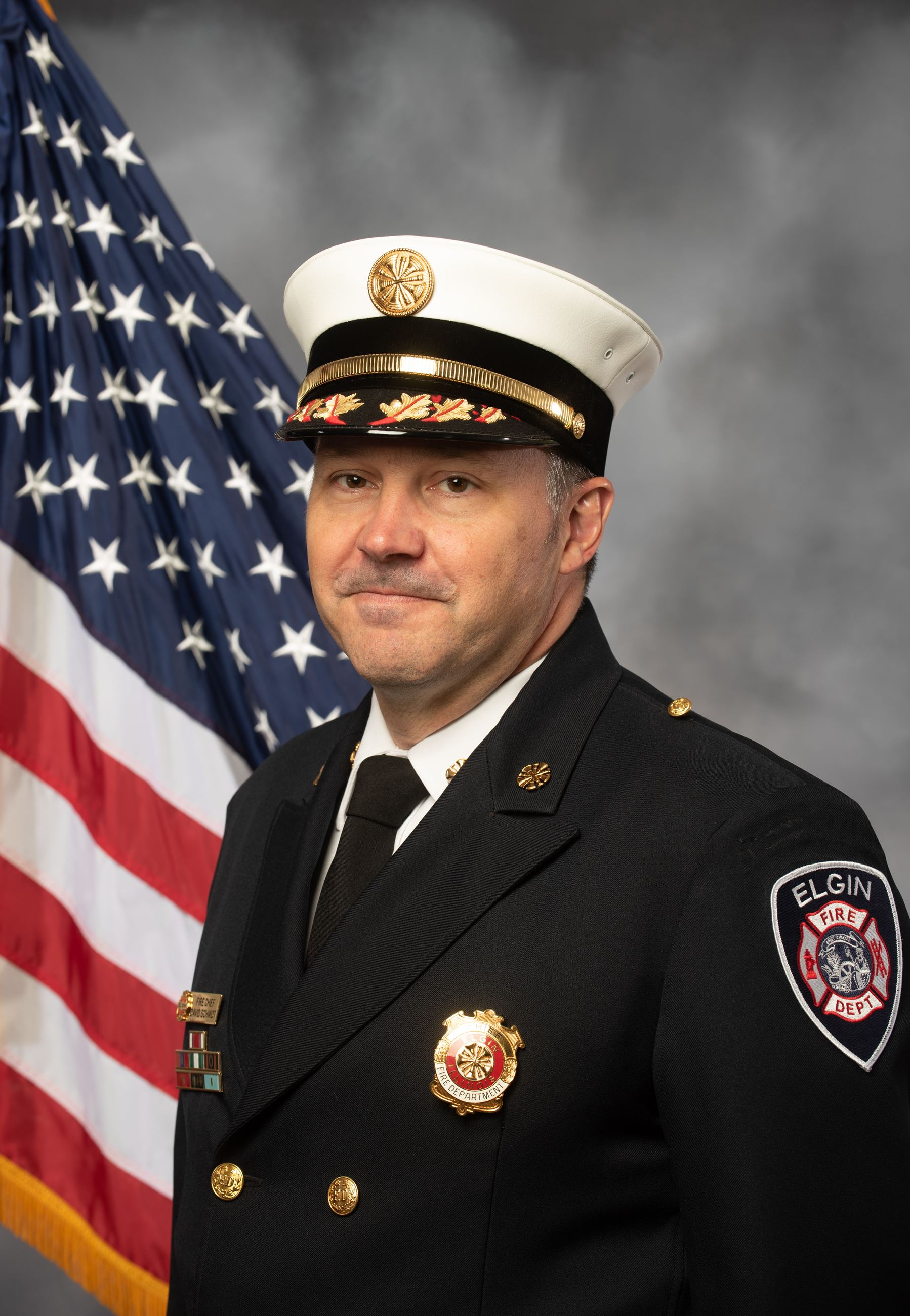 Chief David Schmidt headshot photo with American flag