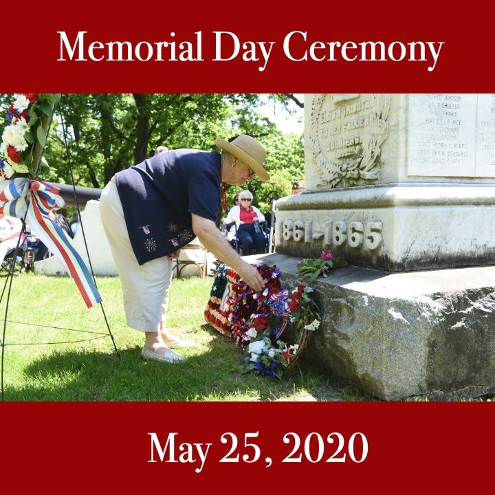 Memorial Day 2020. Woman laying flowers on a gravestone.