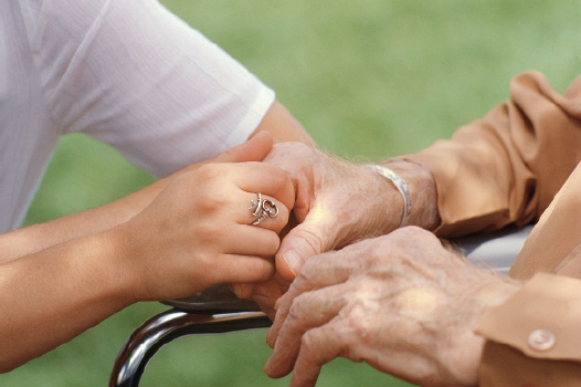 person holding hand of an elderly senior